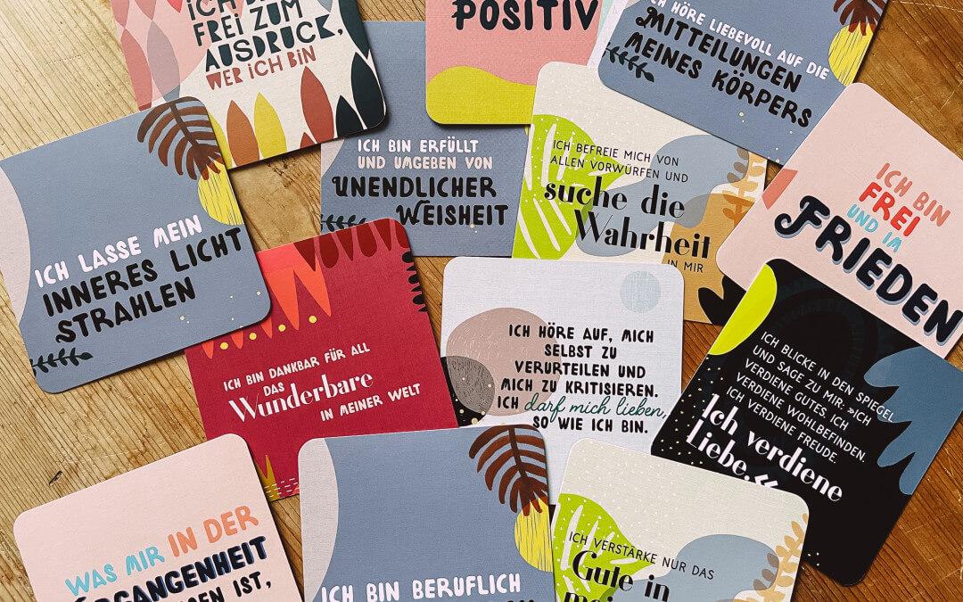 Auf einem Tisch liegen viele bunte Karten mit Affirmationen.